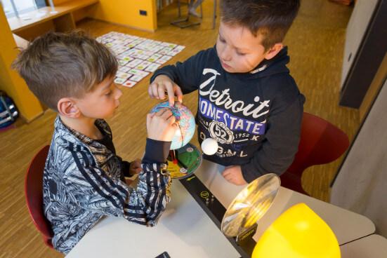 Schüler untersuchen einen Globus