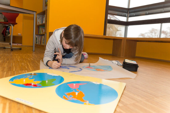 Schülerin arbeitet mit Kartenmaterial