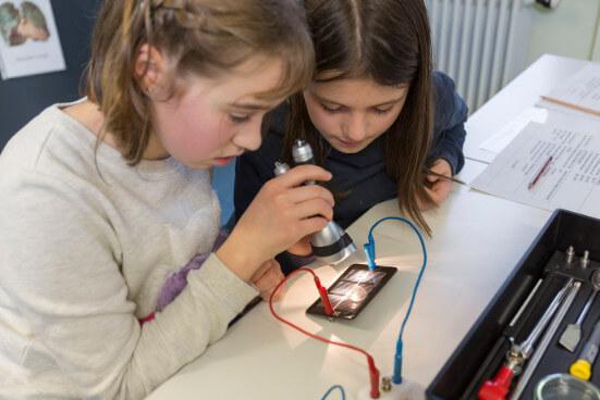 Schülerinnen unetrsuchen eine Photovoltaikzelle