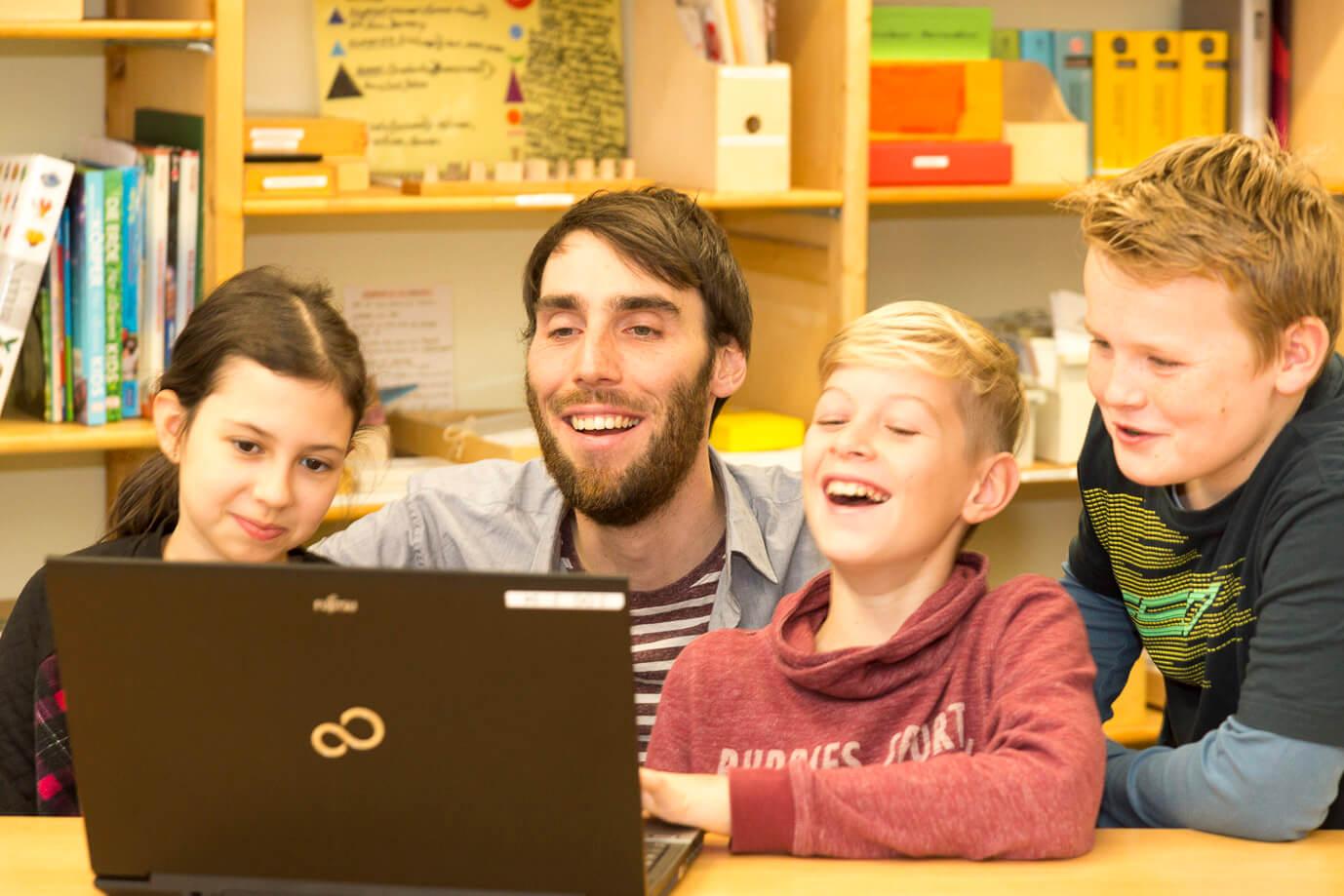Mehrere Schüler mit Lehrer am Laptop